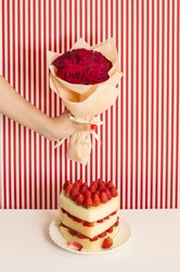 Women's hand holding red rose bouquet on retro style background over a heart shape strawberry cake. Valentine's Day image.