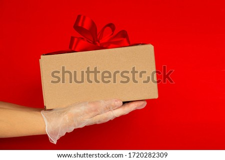 Women's hand in medical gloves hold a gift box with a red ribbon on a red background. Concept of sales and gifts during Coronavirus. Quarantine. Delivery courier. Online purchase