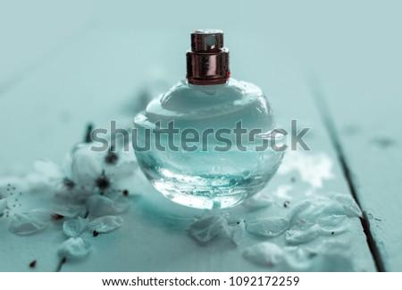 Women's hand spray perfume. Flower arrangement. Flowers, fragrance, perfume on pink background #1092172259