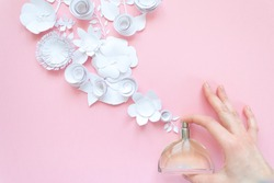 Women's hand spray perfume. Flower arrangement. Flowers, fragrance, perfume on pink background. Cut from paper