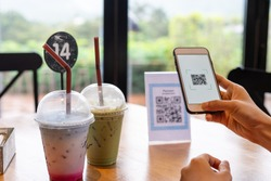 Women's hands are using  the phone to scan the qr code to select food menu. Scan to get discounts or pay for food. The concept of using a phone to transfer money or paying money online without cash.