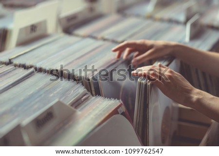 Women's hands browsing records in a vinyl record store