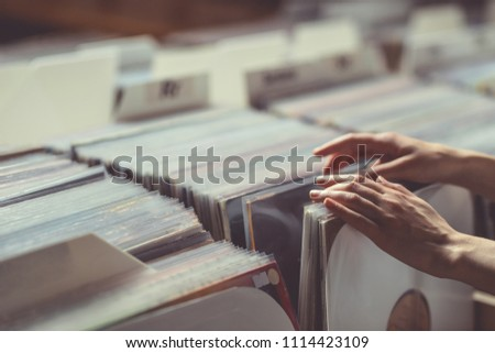 Women's hands browsing vinyl records close-up