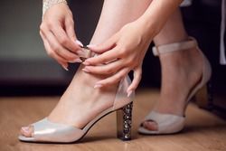 Women's hands fastening shoes on the floor