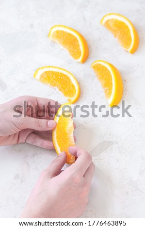 Women's hands hold juicy orange slices on the table