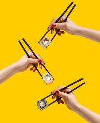 Women's hands hold sushi rolls with sticks. Yellow background. Creative concept