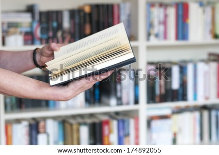 Women\'s hands holding a book in his hand in front of a bookshelf.