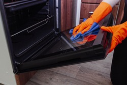 Women's hands in gloves with a microfiber cleaning cloth clean the oven door