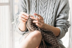 Women's hands knit. The girl knits at the window. Gray sweater.