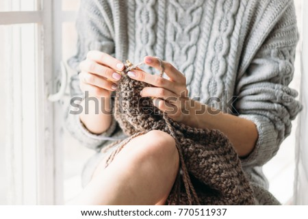 Women's hands knit. The girl knits at the window. Gray sweater. Foto d'archivio ©