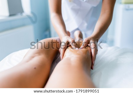 Women's hands massage the athlete's legs and shins after the competition. Sports massage, recovery. Sports medicine. Phlebeurysm. Photo stock ©