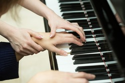 Women's hands on the keyboard of piano. girl plays. music teacher