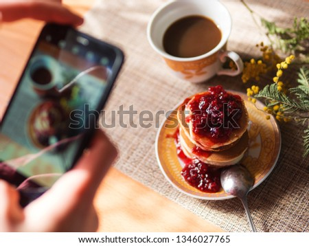 Women's hands take pictures of Japanese pancakes with jam