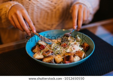 Women's hands using fork and knife for caesar salad served in bowl. Close-up view. Lunch at restaurant. #1012650550