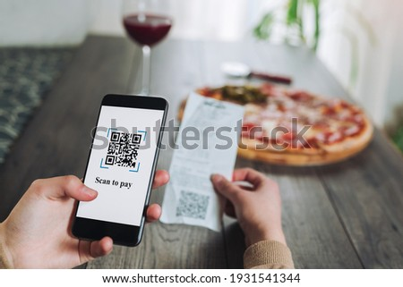 Women's hands using the phone to scan the qr code to pay pizza. Scan to get discounts or pay for pizza. The concept of using a phone to transfer money or paying money online without cash.FAKE QR.
