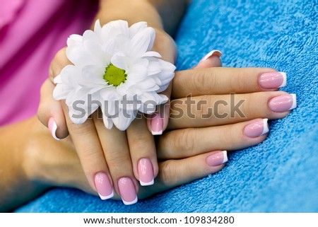 Women's hands with french manicure and flower
