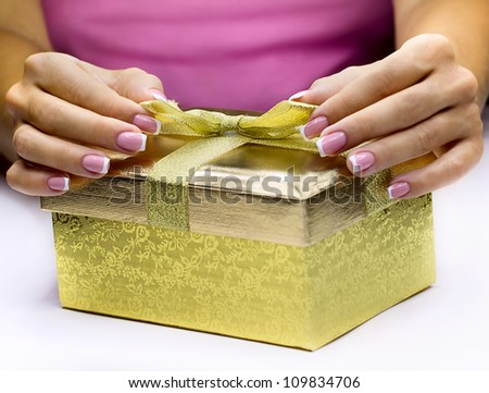 Women's hands with french manicure opening gift  box