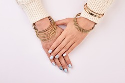 Women's hands with gold bracelets. Blue manicure with rhinestones.