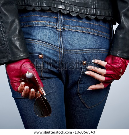 Women's hands with the sunglasses in stylish gloves back on the background of jeans