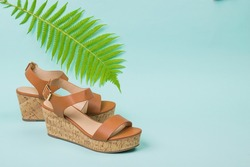 Women's high-soled sandals with a fern leaf on a blue background. Concept of recreation by the sea.
