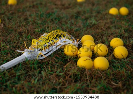Women's lacrosse stick laying on a lacrosse field with yellow lacrosse balls.