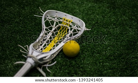 Women's lacrosse stick next to yellow lacrosse balls.