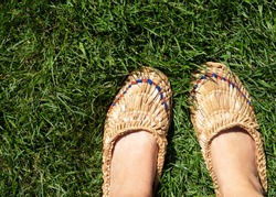 Women's legs are dressed in a pair of old bast shoes stand on the grass.