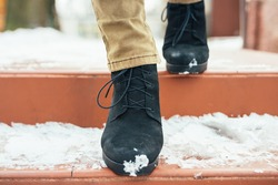 Women's legs in elegant winter boots down the snow-covered stairs, close-up