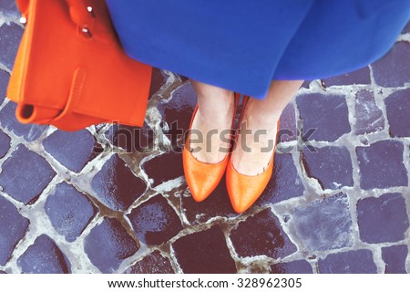 Women\'s legs in orange shoes. Bright orange shoes and bag. Blue coat, orange classic ladies shoes and tote bag. Rainy day. Street fashion. Street style. Business casual look. Autumn outfit.