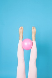 women's legs in pink sports leggings hold a rubber Pilates ball between them, isolated on a blue background.