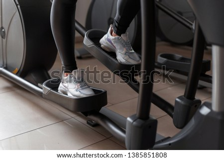 Women's legs in white sneakers working on the stepper simulator in the gym. Girl doing exercises in a health club. Close-up.