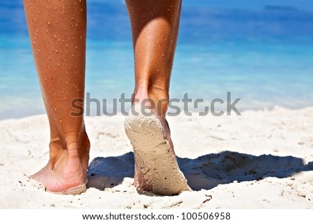 Women's legs on a sandy beach, Maldives