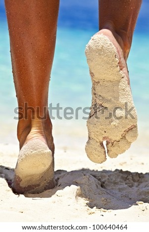 Women's legs on a sandy beach, Maldives - stock photo