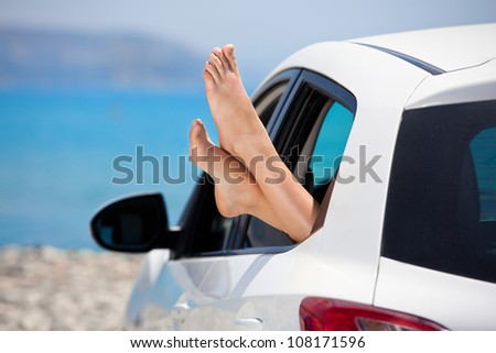 Women's legs sticking out the car window . The concept of relaxation and travel