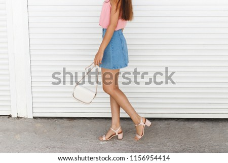 Women's legs. Woman wearing denim mini skirt, pink block heeled sandals, cross body bag with chain strap walking near white roller door. Details of trendy casual outfit. Everyday look. Street fashion. #1156954414