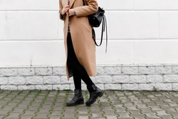 Women's legs. Woman wearing long beige coat, black boots and leather backpack walking through the city streets. Trendy casual outfit. Details of everyday look. Street fashion.