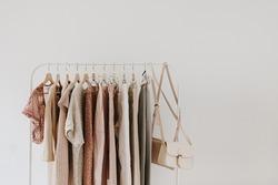 Women's minimal fashion pastel clothes. Stylish female blouses, sweaters, pants, jeans, t-shirts, handbags on hanger on white background. Fashion blog, website, social media hero header.