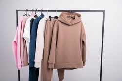 Women's minimal fashion pastel clothes. Stylish female t-shirts, hoodie, pants on hanger on white background. Spring cleaning home wardrobe. High quality photo