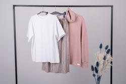 Women's minimal fashion pastel clothes. Stylish female t-shirts, hoodie, pants on hanger on white background. Fashion blog, website, social media hero header. High quality photo