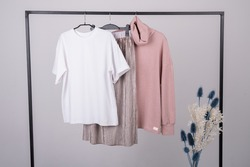 Women's minimal fashion pastel clothes. Stylish female t-shirts, hoodie, pants on hanger on white background. Fashion blog, website, social media hero header.