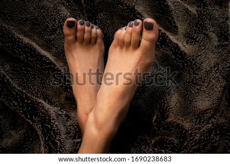 Women's painted toes on fur blanket.