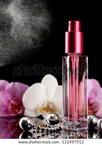 women's perfume in beautiful bottle and orchid flowers, on black background