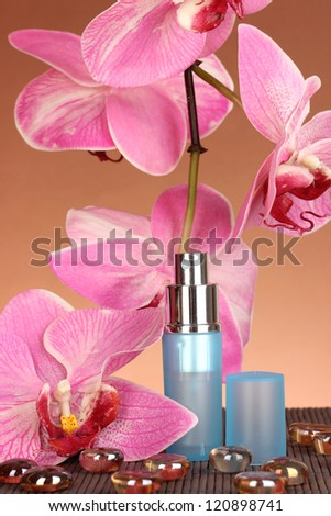 Women's perfume in beautiful bottle with orchids on brown background