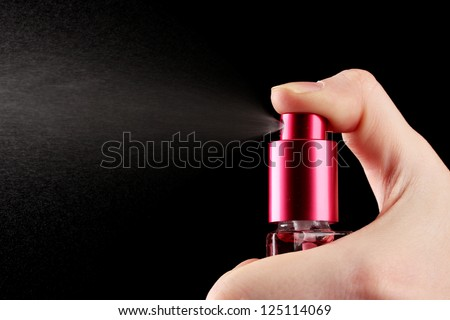 women's perfume in bottle and spraying, on black background
