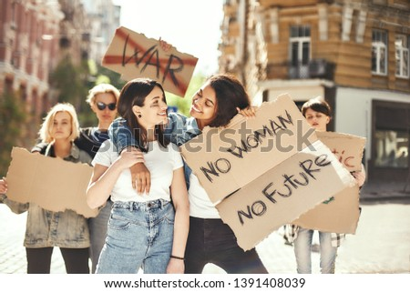 Women s rights are human rights. Two happy young women are holding signboards and smiling while standing on the road around female activists. #1391408039