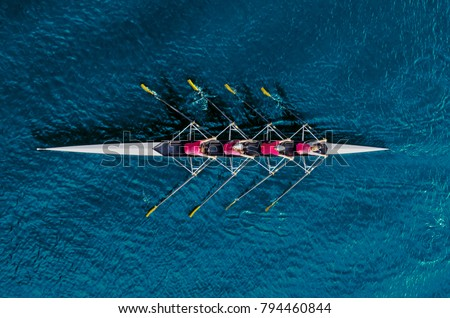Photo of Women's rowing team on blue water, top view