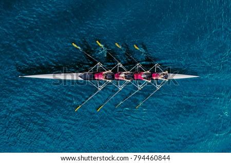 women's rowing team on blue...