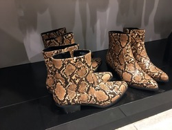 Women's Snakeskin Cowboy Boots. Snake Cowboy Ankle Boots for display to sell on shoes store. Mass market shop. Close View Of Fashion Casual Female shoes. Brown snake Print Women Boots