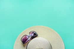 Women's Straw Hat Fashionable Sun Glasses on Turquoise Background