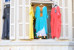 Women's stylish oriental style ethnic dresses in store at display window, in summer street market. Modern  fashion shop / Textile souk (bazaar) with colorful  tunics in window.
